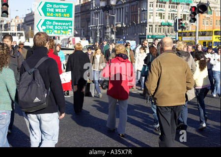 pedestrians crossing the road at traffic lights at oconnell bridge in dublin - Stock Photo