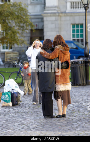 tourists taking posed photos in parliament square inside Trinity College Dublin University of Dublin - Stock Photo