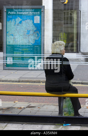 old grey haired woman sits at bus stop with tescos recyclable shopping bag waiting for a bus in belfast city centre - Stock Photo