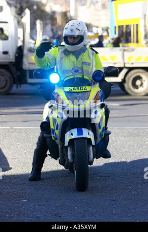 garda siochana irish police force traffic police cop on motorbike with one leg on the ground waving people on - Stock Photo