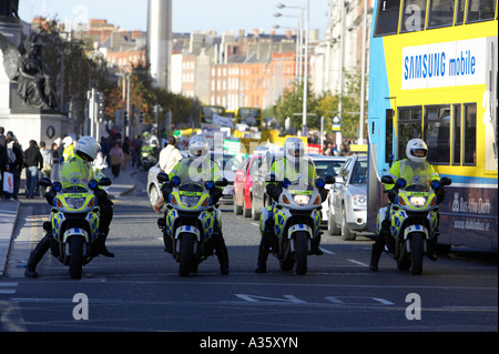 four garda siochana irish police force traffic police cops on motorbikes at front of demonstration on liffey bridge - Stock Photo