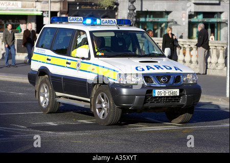 garda siochana irish police force cop officer in 4x4 police vehicle on liffey bridge in dublin with blue light flashing - Stock Photo
