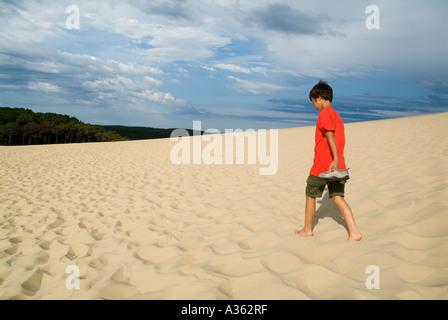 Boy walking on the Pyla great sand dune on Bassin d Arcachon France Aquitaine - Stock Photo