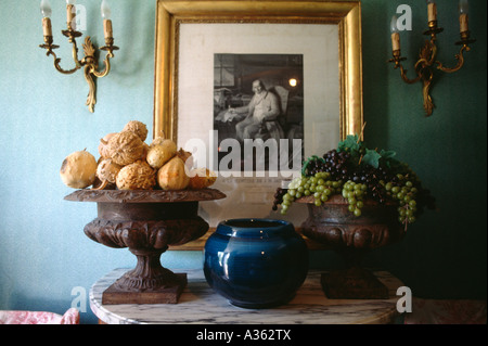 Close-up of bowl of walnuts and gourds with blue glass vase and bowl of grapes on table in front of picture on wall - Stock Photo