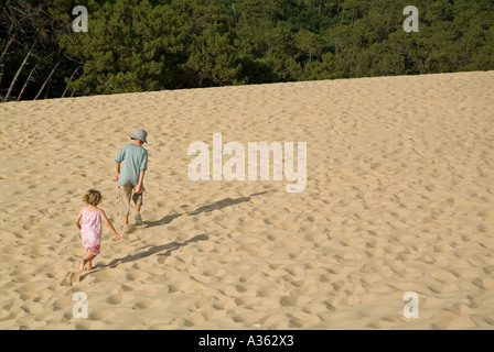 Brother and Sister walking on the Pyla great sand dune on Bassin d Arcachon France - Stock Photo