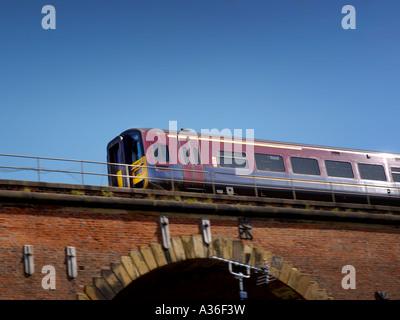 UK regional passenger train passing over brick bridge against blue sky - Stock Photo
