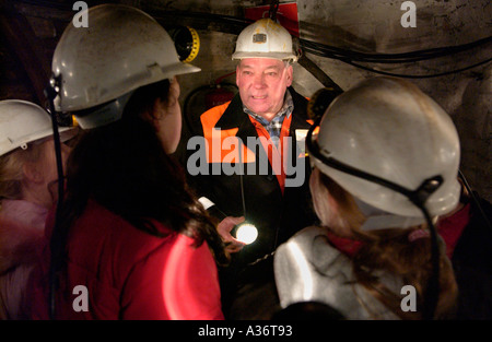 Guide a former miner giving school pupils an underground tour at Big Pit National Coal Museum Blaenavon South Wales - Stock Photo