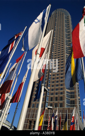 National flags in front of Frankfurt Messeturm trade fair tower - Stock Photo