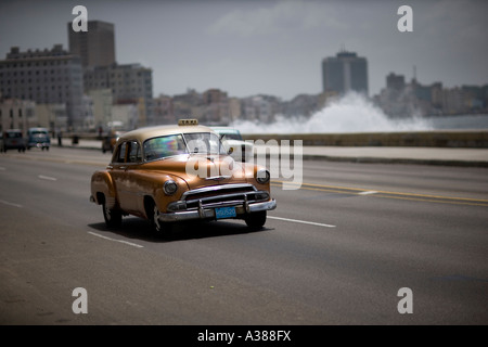 A vintage gold Chevy drives along El Malecon while waves crash along the seawall - Stock Photo