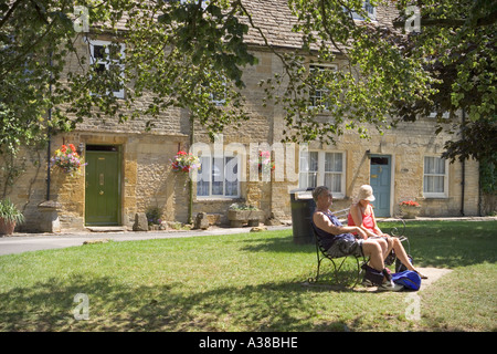 Visitors relaxing in a corner of the Market Square in the Cotswold town of Stow-on-the-Wold, Gloucestershire - Stock Photo