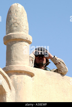 A US Army soldier uses binoculars to scan for Anti Iraqi Forces in a cemetary in Iraq. - Stock Photo