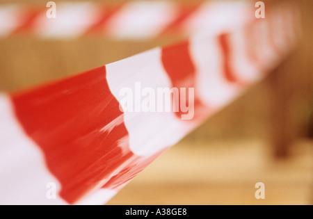 Red and white banded plastic tape temporarily keeping the public from entering a works or hazard zone - Stock Photo