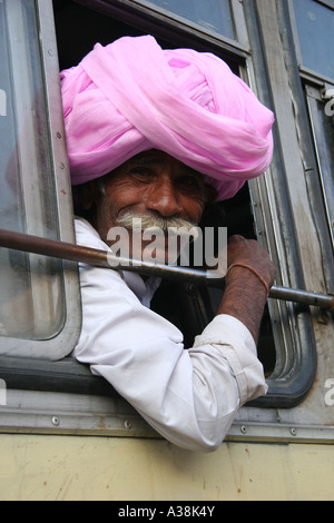 Indian man on a bus wearing a pink turban outside the City Palace in the centre of Jaipur, the pink city of India - Stock Photo