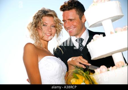 Brautpaar im Freien, mit Hochzeitstorte, bridal couple outside with weddingcake - Stock Photo