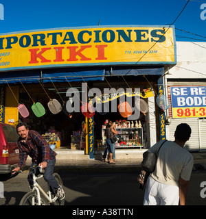 Shop selling various goods on a street in Mazatlan Sinaloa Mexico whilst a cyclist passes to the left. - Stock Photo