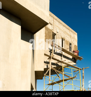 Man Working On Scaffolding On Block Of Flats Building