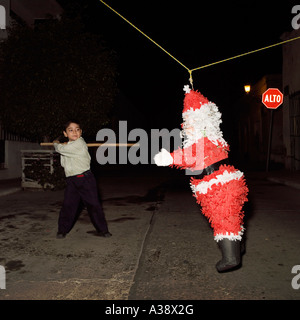 A young boy hits a Santa Claus Father Christmas pinata with a stick in Mazatlan Sinaloa Mexico - Stock Photo