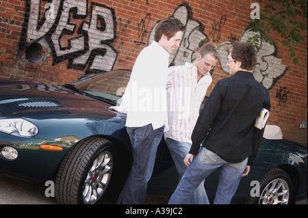 Group of guys hanging around car - Stock Photo