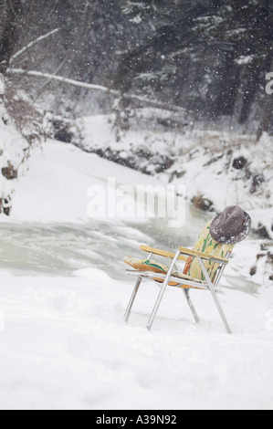 Garden chair left out in the snow - Stock Photo