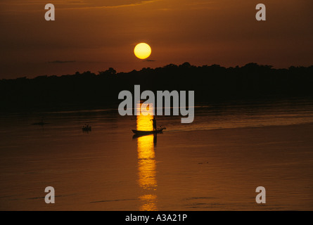 congo river with pirogue sunset - Stock Photo