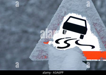 warning sign slippery road in winter germany - Stock Photo