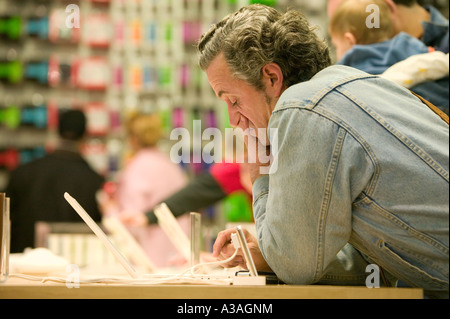 Customer reviewing email on an iBook in the Fifth Avenue Apple retail store New York City New York - Stock Photo