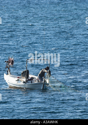 Fisherman Casting fishing net off the stern of his boat. Paphos Cyprus - Stock Photo