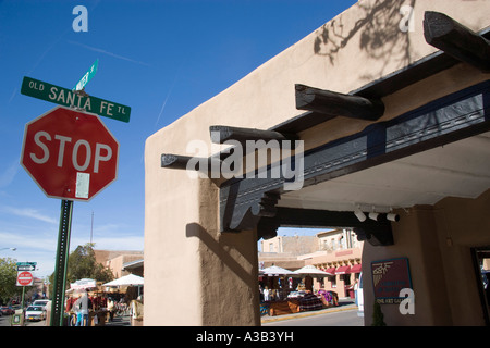 USA New Mexico Santa Fe Stop sign on the Old Santa Fe Trail beside adobe Pueblo Revival style building with market - Stock Photo