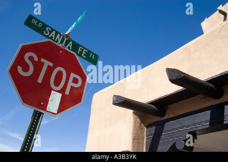 USA New Mexico Santa Fe Stop sign on the Old Santa Fe Trail beside an adobe Pueblo Revival style building - Stock Photo