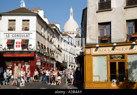 FRANCE Ile de France Paris Montmartre Tourists in narrow streets between boulangerie and Consulat Restaurant near - Stock Photo