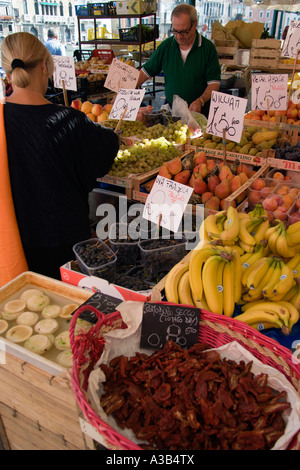 ITALY Veneto Venice Fruit and vegetable stall in the Rialto Market on Grand Canal with vendor serving local female - Stock Photo