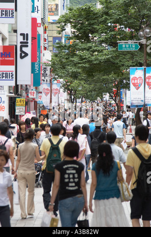 Shoppers Walking Along Busy Street - Stock Photo