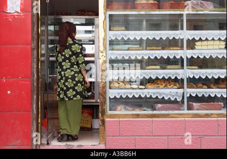 Woman Inside Cake Shop - Stock Photo