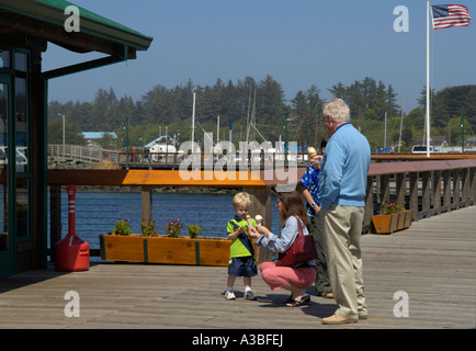 Family eating ice cream cones on the boardwalk in Oldtown Bandon on the southern Oregon Coast - Stock Photo