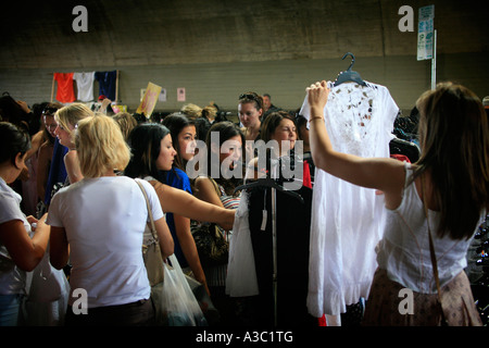 Young women bargain hunting at market - Stock Photo