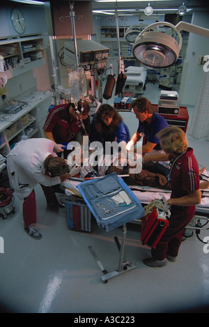Overhead view of doctors nurses and paramedics working on patient in hospital trauma room Minneapolis MN - Stock Photo