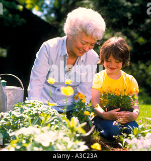 Grandmother and granddaughter working in the garden preparing to plant flowers - Stock Photo