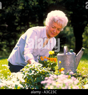 Senior citizen lady working in her garden preparing to plant flowers and water them - Stock Photo