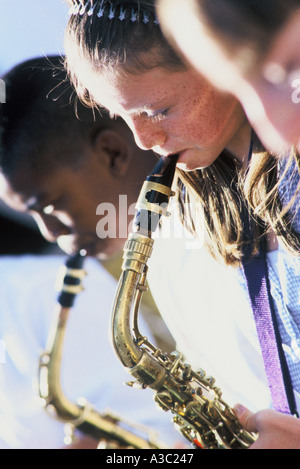 Close up of three sixth grade students playing saxophone in a middle school concert - Stock Photo