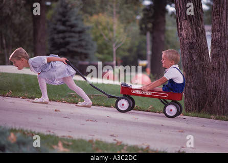 Sister pulling her younger brother who is sitting in a red wagon up a steep hill - Stock Photo