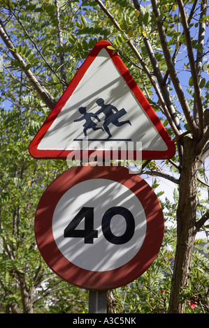 european style triangular red warning children crossing and 40 km h round speed traffic signs in trees - Stock Photo