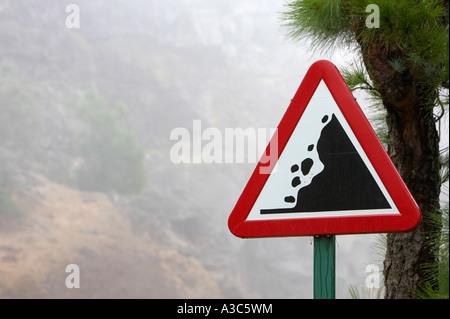loose falling rocks warning triangular roadsign on the mountain road to El Teide Tenerife Canary Islands Spain - Stock Photo