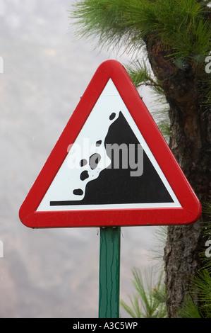 loose falling rocks warning triangular roadsign on the mountain road to El Teide Tenerife Canary Islands Spain vertical - Stock Photo