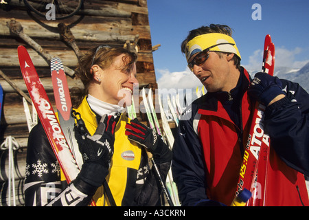 couple with cross-country ski in front of a wooden hut, Austria, Alps - Stock Photo