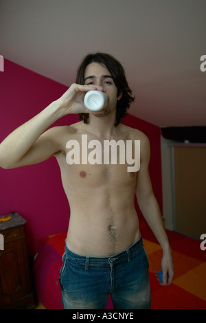 Young man bare chested drinking milk from bottle - Stock Photo