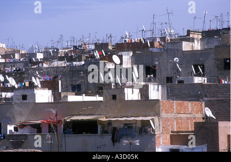 TV aerials and satellite dishes on rooftops in Fez Morocco Some roofs have washing hung out to dry in the sun - Stock Photo