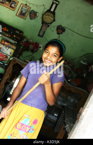 Environmental portrait of pretty young girl sweeping the front room of her home, Sri lanka - Stock Photo
