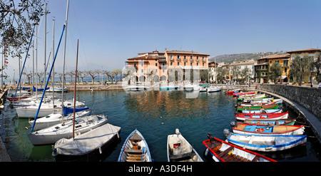 Harbour with sailing ships and small fishing boats, Torri del Benaco, Garda lake, Italy - Stock Photo