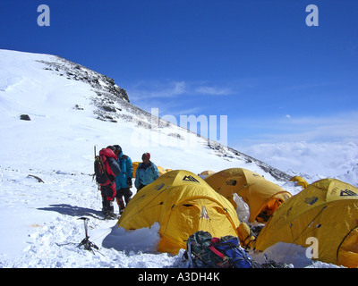 Yellow tents, alpinists and equipment in Camp IV, 4, on South Col, 7950m, Mount Everest, Himalaya, Nepal - Stock Photo