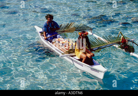 Two women in traditional dress delivering breakfast by outrigger canoe, Sheraton  Moorea Hotel, Tahiti - Stock Photo
